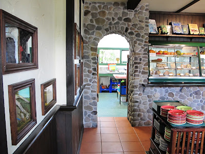 Inside of Mr Badger's cafe at Tawhiti Museum, with a wall of one-twelfth-scale miniature scenes set into the left wall.
