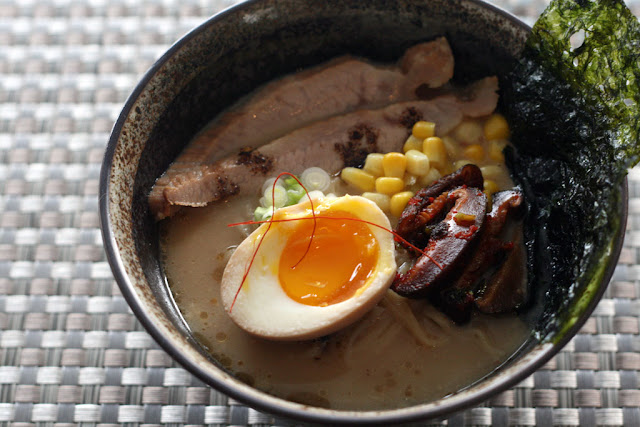 A bowl of ramen with a soft boiled egg, pickled mushrooms, char siu pork, corn, and sea weed.