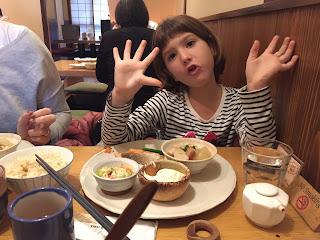 Paula saludando con la comida delante, salmón,ensalada y arroz