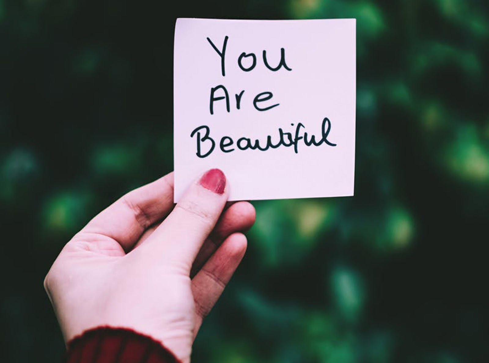 a woman holding a piece of paper that says you are beautiful