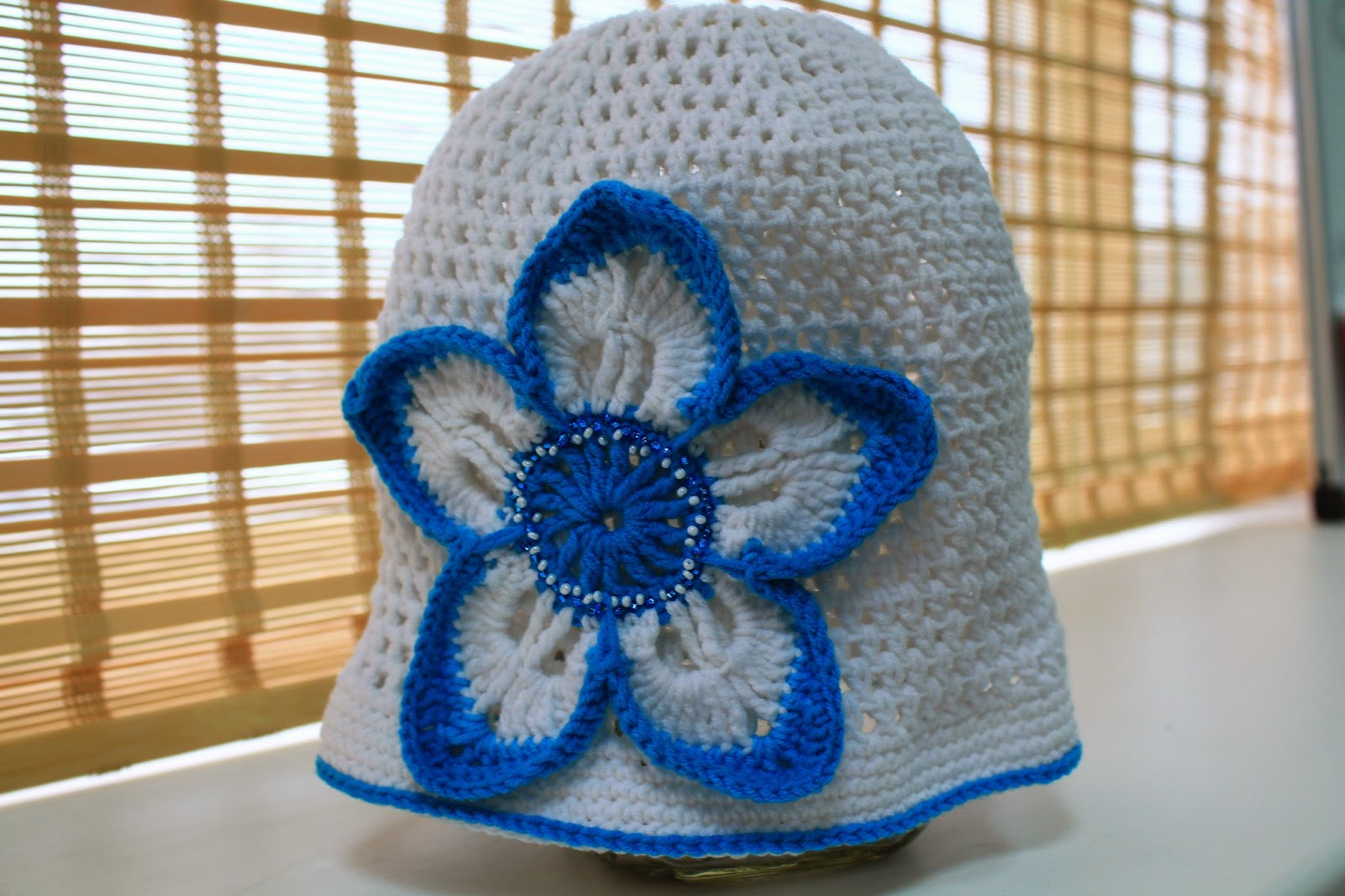 crochet hat with a blue flower