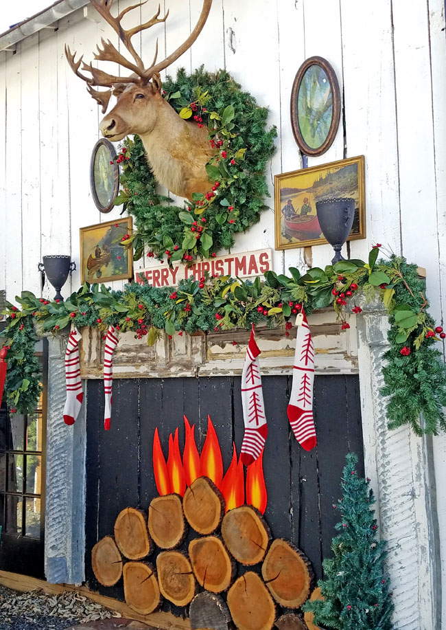 big fireplace mantel with deer head and stockings