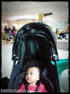 gambar Aina sedang duduk dalam stroller bayi menunggu giliran bertemu doktor pakar jantung kanak-kanak di Hospital Serdang