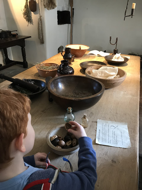 Little boy looking at items on an old wooden table. Items are in wooden bowls from the period.