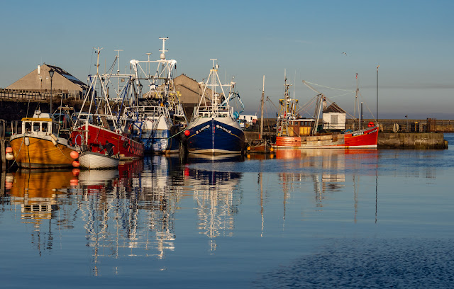 Photo of colourful fishing boats refelected in the still water at Maryport Harbour
