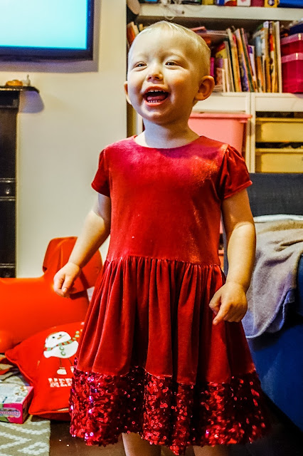 Little in a red velvet dress with sequins at the bottom laughing, dress from M&S and lots of mess in the background