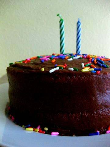 A Classic Yellow Cake Covered In Chocolate And Topped With Sprinkles Two Candles Its His Birthday Afterall