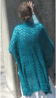 A woman with her back to the camera.  A large green-blue lace shawl is over her shoulders.  The shawl is square and hangs down over her back.