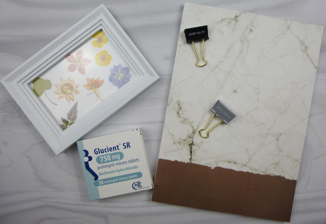 Marble notebook, white photo frame and packet of Metformin on white, wooden background