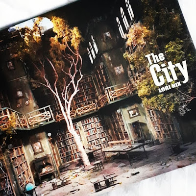 Front cover of the book 'In the city' by Lori Nix showing a two-storied library space in a state of neglect, with a tree growing out of the floor and through a hole in the ceiling.
