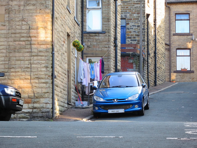 Blue car outside house on a hill with washing outside.