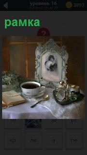 На столе чашка чая с ложкой и в рамке портрет женщины, рядом лежит развернутая книжка
