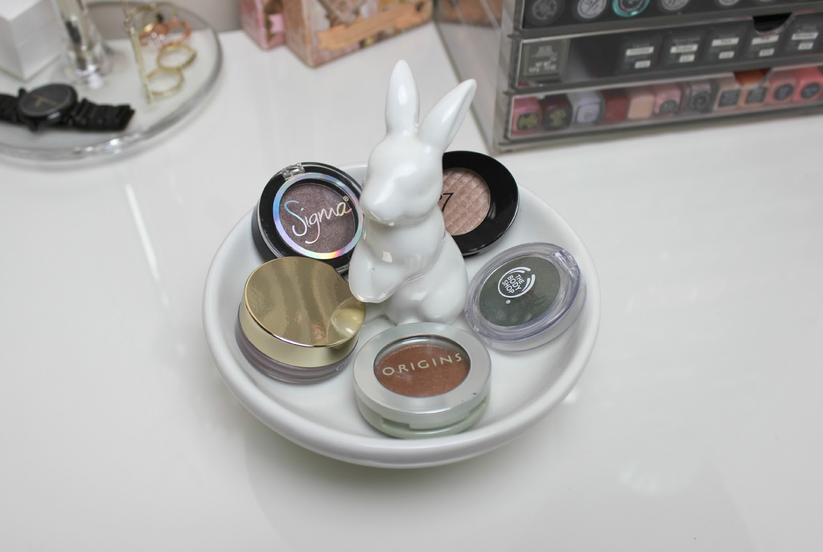 A picture of individual eyeshadows in a white rabbit jewellery dish