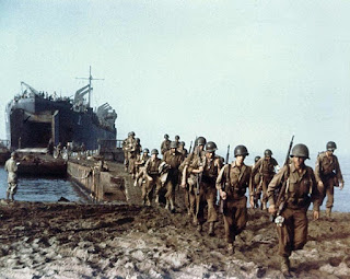 American troops disembark from a US Navy tank ship across a causeway set up by the beach at Palermo