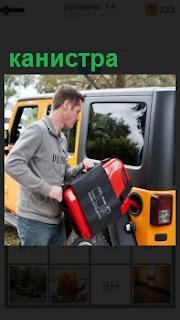 Водитель мужчина заправляет из канистры бензином свою машину