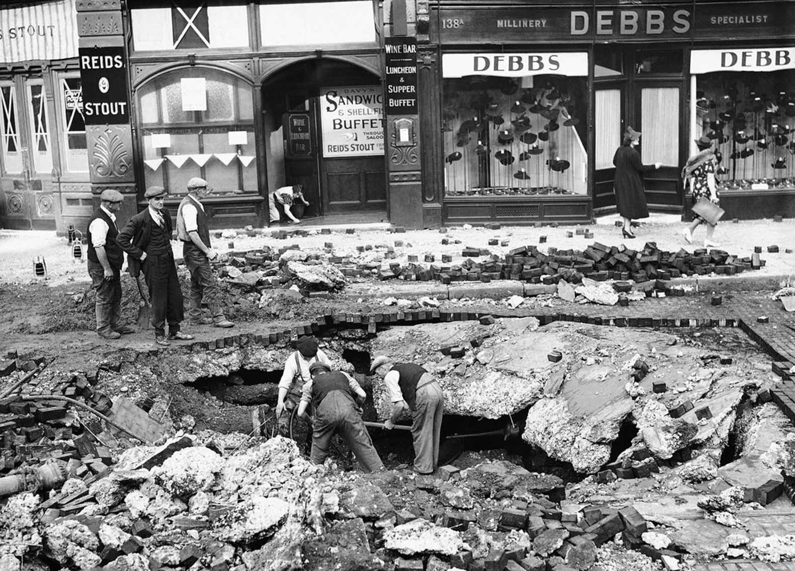 A huge crater was made in a road at Elephant & Castle, London on September 7, 1940, after a night raid on London.