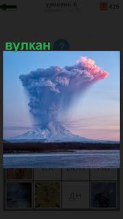Вдали за водоемом виден дымящийся вулкан, дым высоко поднимается в небо
