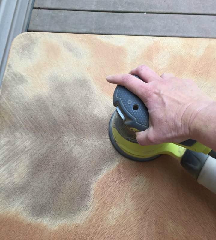 Sanding with an orbital sander.