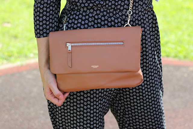A lovely lady wearing a caramel leather clutch bag with chain strap.