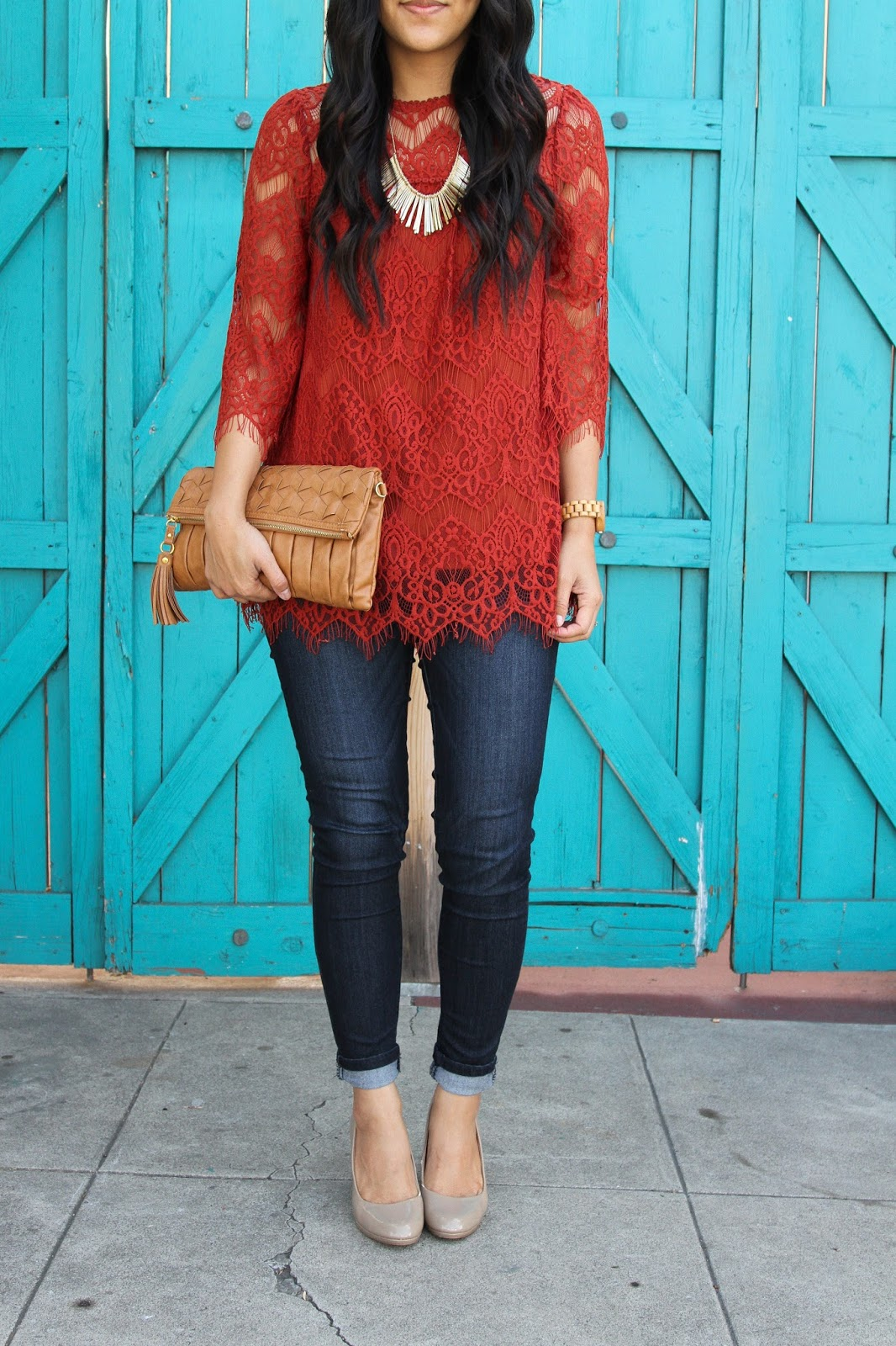 rust orange lace top + dark wash jeans + nude pumps + tan woven clutch + gold statement necklace