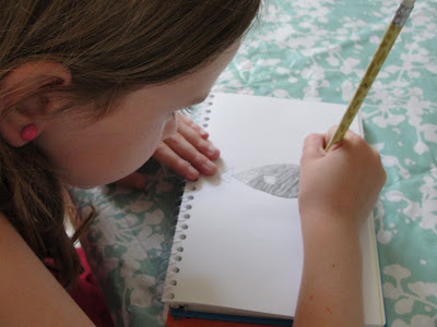 child sketching a fish