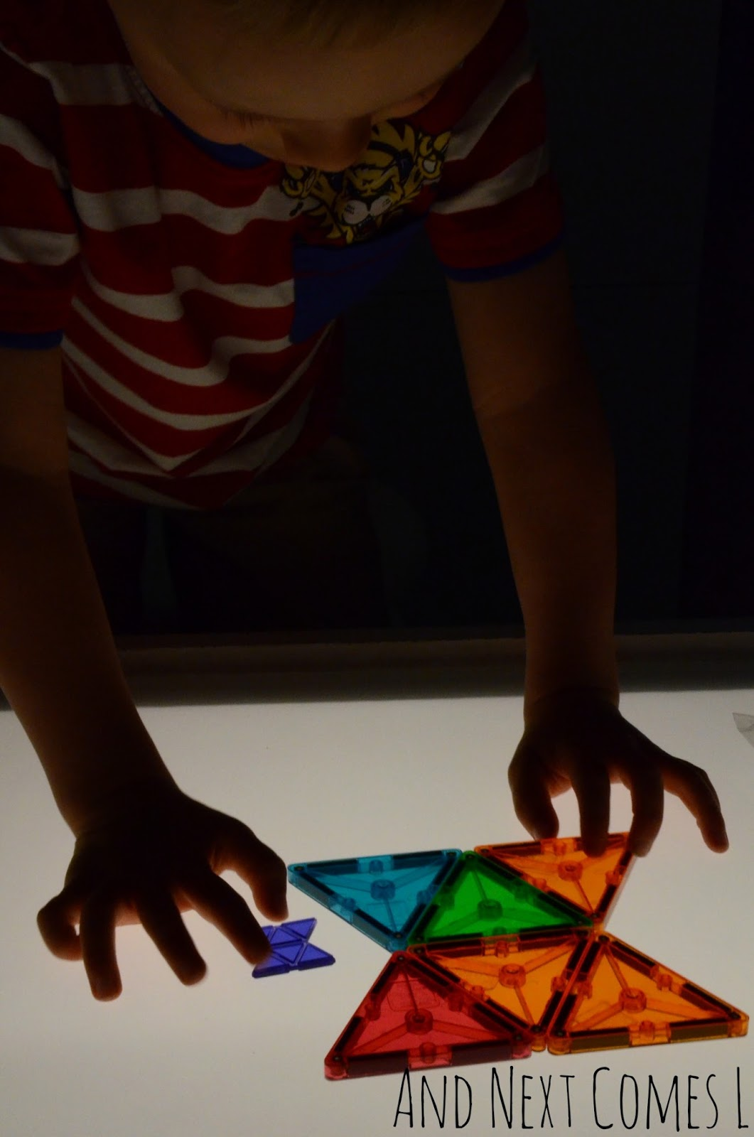Using Magna-Tiles to recreate shapes on the light table from And Next Comes L