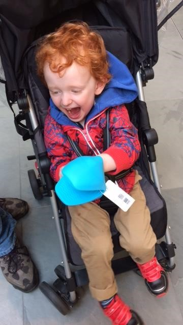 Little boy sitting in a pushchair, playing with an oven mitt and laughing