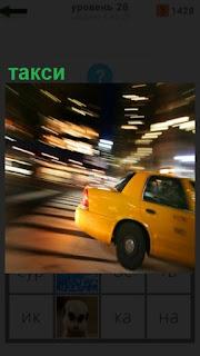 едет желтое такси на большой скорости по улице города