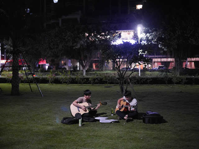 two young men sitting on the grass playing acoustic guitars at night in Zhuhai