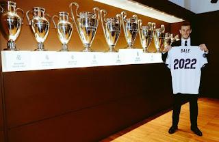 Gareth Bale posa con la camiseta de renovación hasta 2002 en la sala de trofeos del Real Madrid
