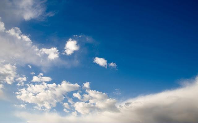 Foto van een blauwe lucht met enkele wolken