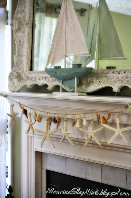 sea side living room with a shell garland and blue sail boat on the mantle of the fireplace | rosevinecottagegirls.com