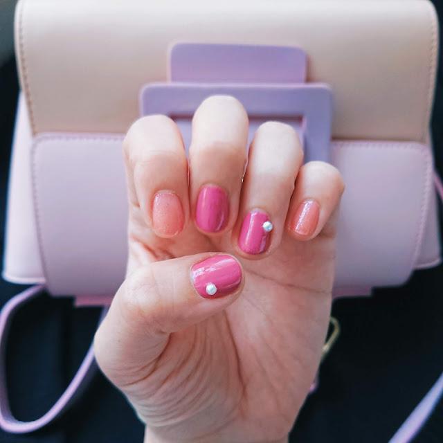 タイプの違うピンクカラー2色とパールのパーツをのせたピンクネイル。