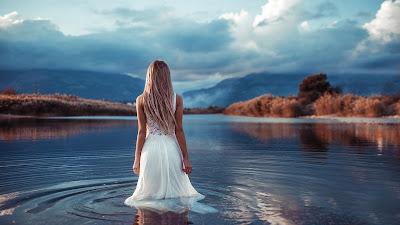 Chica rubia de vestido blanco metida en un lago viendo las montañas con nubes