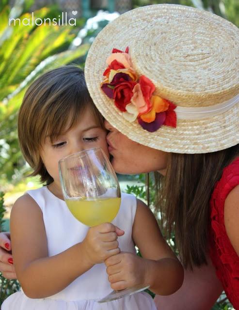 Invitada con canotier de copa baja, cinta blanca y flores en tonos rojos y naranja de marca malonsilla, vestido rojo y pelo suelto dándole un beso a una niña