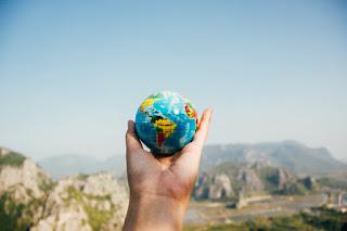 El mundo en tus manos mano extendida con pequeño globo terráqueo.