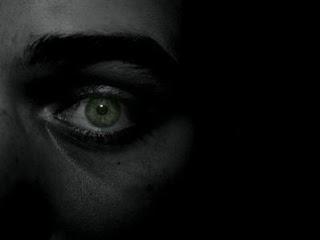 Cara de una persona en la oscuridad en la que solo se ve un ojo, de color verde, con expresión asustada.