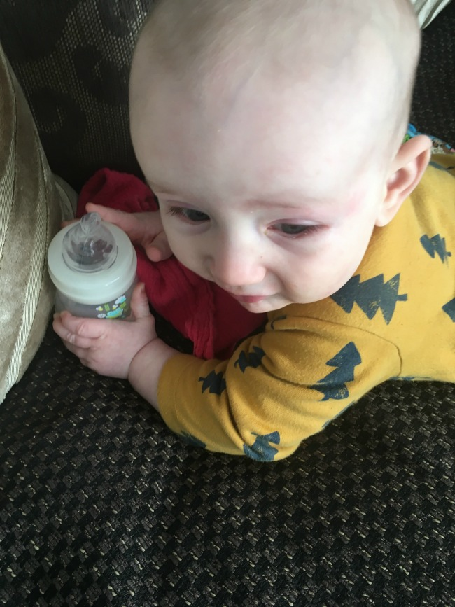 baby-lying-on-front-holding-bottle