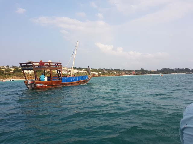 a wooden sail dhow on the ocean, with the Nungwi coast on the background