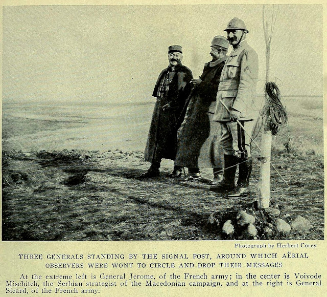 THREE GENERALS STANDING BY THE SIGNAL POST, AROUND WHICH AERIAL OBSERVERS WERE WONT TO CIRCLE AND DROP THEIR MESSAGES At the extreme left is General Jerome, of the French army; in the center is Voivode Mischitch, the Serbian strategist of the Macedonian campaign, and at the right is General Sicard, of the French army.