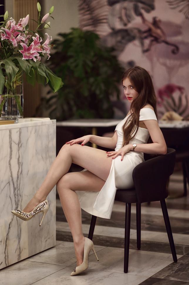 Biała sukienka z rozcięciem, cieliste rajstopy i szpilki zdobione kryształkami
