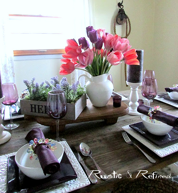 Rustic table setting with tulips and colorful dishes