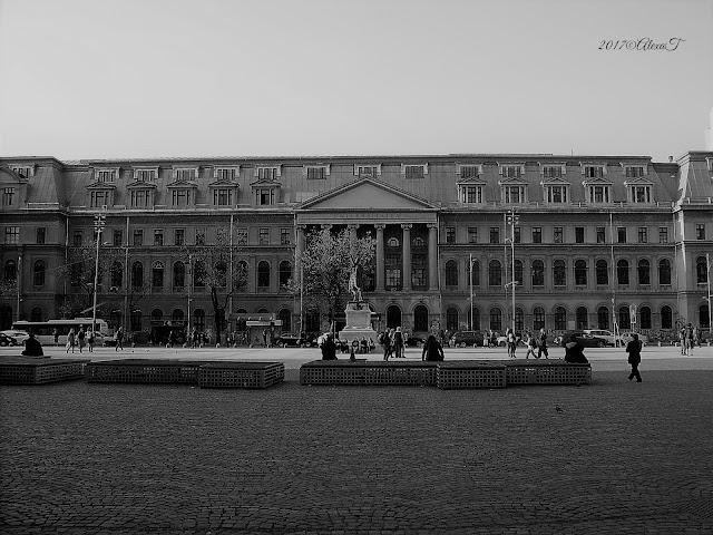 """""""Palatul Universității este o construcție aflată în Piața Universității din București, în perimetrul descris de străzile Regina Elisabeta, Academiei, Edgar Quinet, Nicolae Bălcescu, înaltă de 6 etaje, construită în stil neoclasic pe fostul amplasament al Mănăstirii Sfântul Sava. Construirea viitorului sediu al celei mai mari universități din România, Universitatea București, a început în data de 10 octombrie 1857, după planurile arhitectului Alexandru Orăscu, pe locul fostului colegiu Sfântu Sava, și a fost finalizată la 14 decembrie 1869. Corpurile laterale ale palatului au fost ridicate mai târziu, între anii 1912-1926, după planurile arhitectului Nicolae Ghica-Budești. Palatul Universităţii a devenit post 1989 o scenă a manifestaţiilor de protest Împodobirea exterioară a palatului a fost realizată de către Karl Storck împreună cu asistentul său, Waibel, și un elev de-al său, Paul Focșeneanu."""" Sursa Wikipedia"""