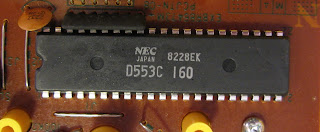 [Image: Close-up photo of a microchip on a PCB, with the etchings 'NEC JAPAN, D553C, 8228EK, 160'.]