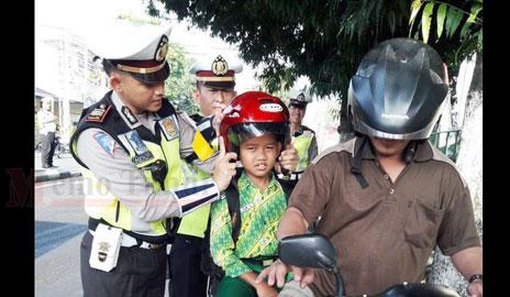 Kasat Lantas AKP Hendry Ibnu Indarto, SH, S.IK saat memasangkan helm kepada salah satu pelajar