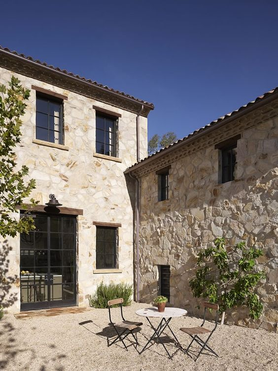 Limestone exterior of #Frenchfarmhouse and #Frenchcourtyard with pea gravel and bistro set on Hello Lovely Studio
