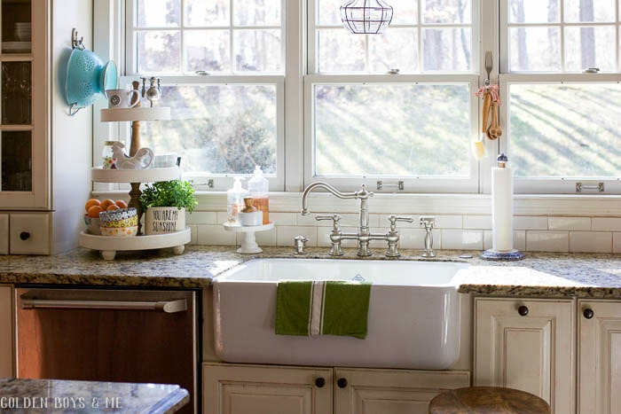 Farmhouse style sink with triple windows above in DIY kitchen