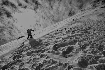 Man climbing a snow-covered hillside with an ice axe