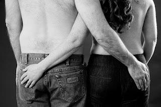 Imagen de un hombre y una mujer de espalda cogiendose el culo