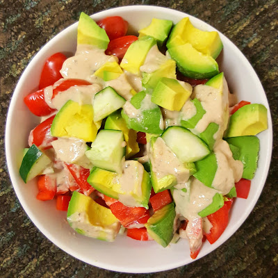 Summer chopped salad with cucumbers, red bell peppers cherry tomatoes and avocado